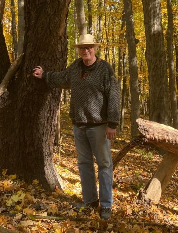 Knute Nadelhoffer stands next to a tree at the forest at the U-M Biological Station. There are fallen yellow leaves on the ground and he's wearing a cowboy-style hat and jeans.