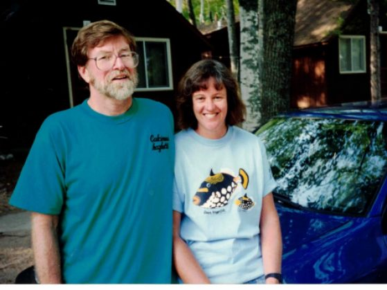 Brian Hazlett and Cathy Bach pose in front of a car at UMBS in the 1990s. Hazlett is wearing his 'calcinus hazletti' t-shirt. Calcinus hazletti is a Hawaiian whitefoot hermit crab; Hazlett is a hermit crab behavior researcher, who discovered and named the species.