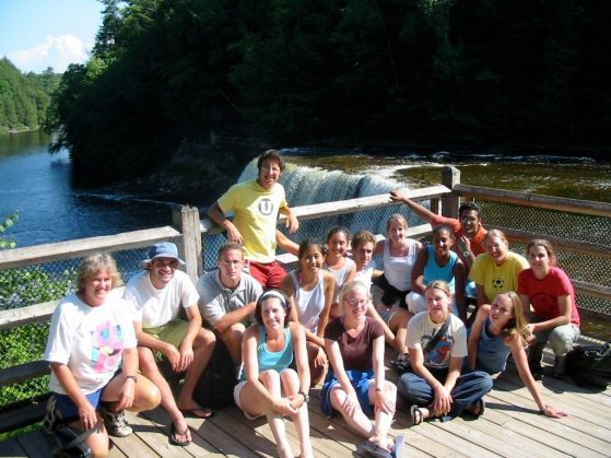 Cathy Bach is pictured with a group of UMBS students. They are posing on a wooden platform that overlooks a waterfall. It is sunny and most are wearing shorts.