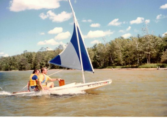 Cathy and Brian sailing a small boat across Douglas Lake.