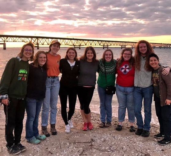 Class standing with the Mackinac Bridge and colorful sunset in the background