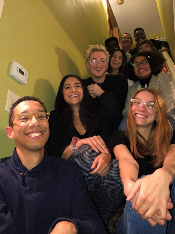 Chris pictured with his MFA poetry cohort sitting on stairs