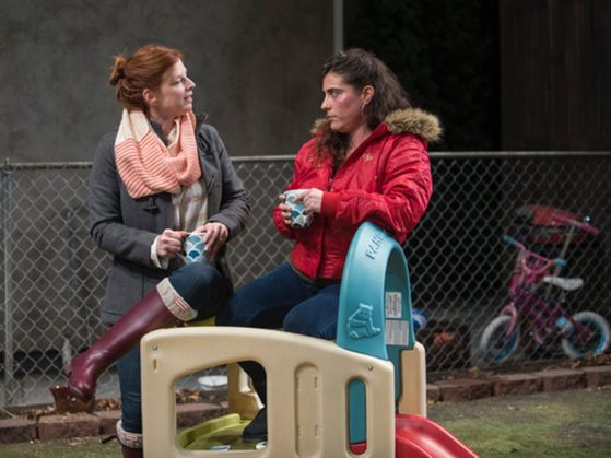 LSWA alum Laura pictured next to another actress in the show CRY IT OUT at Northlight Theatre. They are pictured with a kids little slide playset.