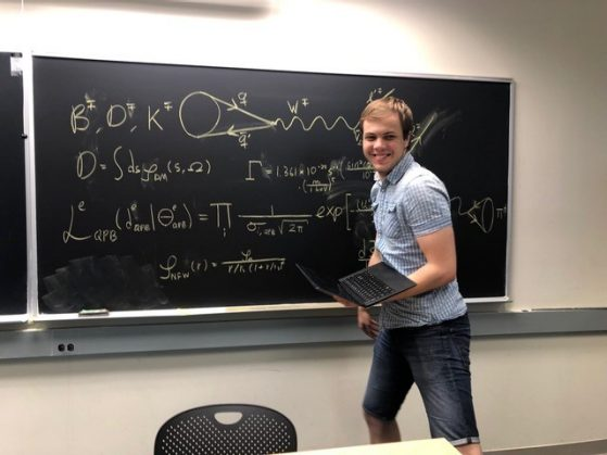 Marius Kongsoere posing in front of a chalkboard with equations on it
