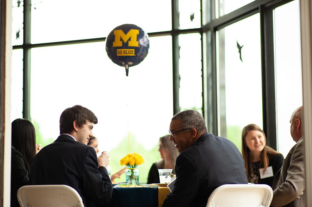 An alum and student seated at a table, with their backs to the camera; they are talking over lunch and smiling. A blue U-M balloon floats above them.