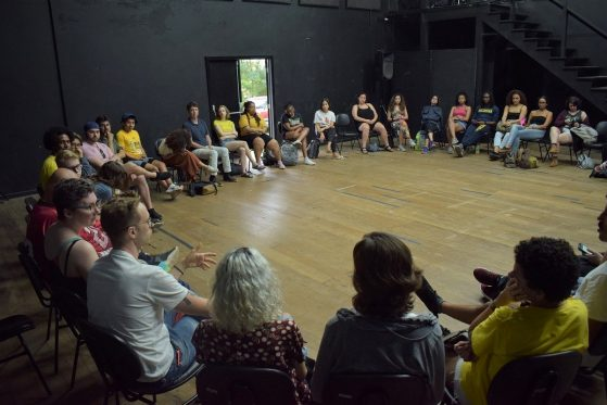 A large group of people sit in a circle in a wood floored rehearsal room in Brazil.