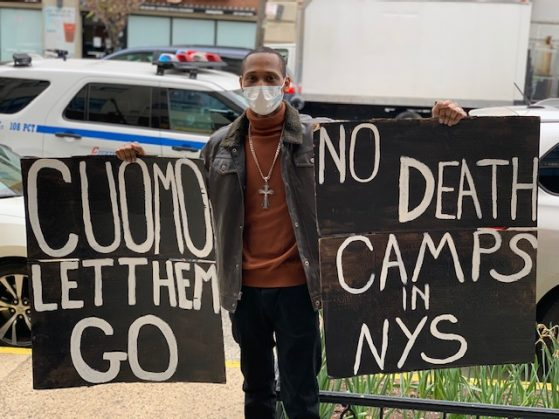 "Man wearing a face mask holding up signs saying ""Cuomo let them go"" and ""No death camps in NYS"""