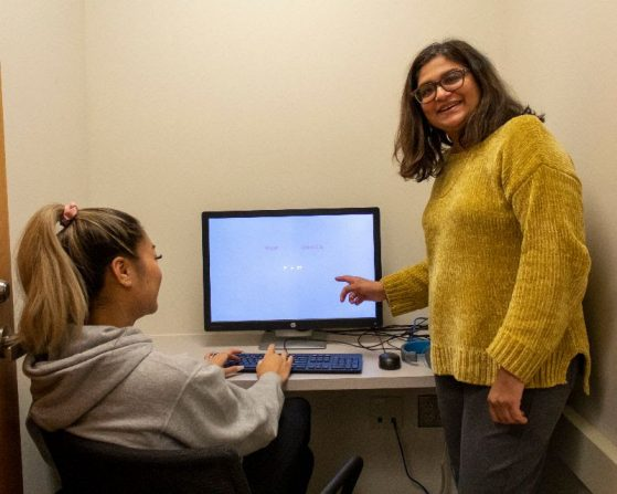 Priti Shah works with undergraduate Quynh Tran testing computerized cognitive tasks.