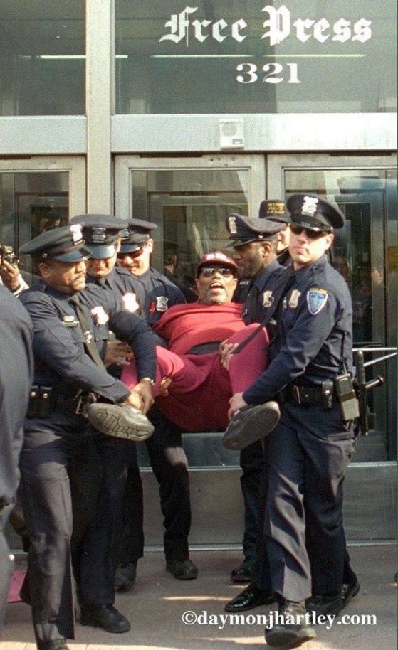 General Baker being removed from a protest by 6 police officers