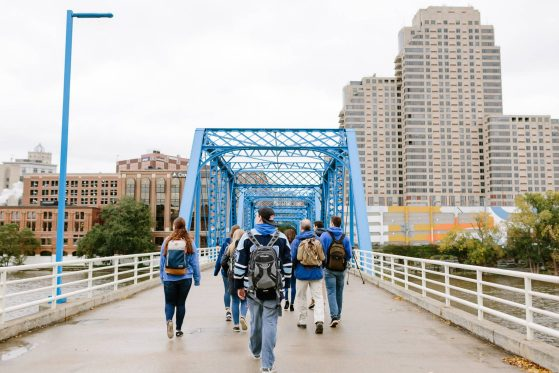 students walk across a blue bridge with large buildings in the background