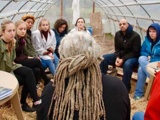 Students sit in hoop house listening intently to man with graying dreadlocks