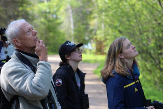 A professor and his students look into a stand of trees, searching for birds.