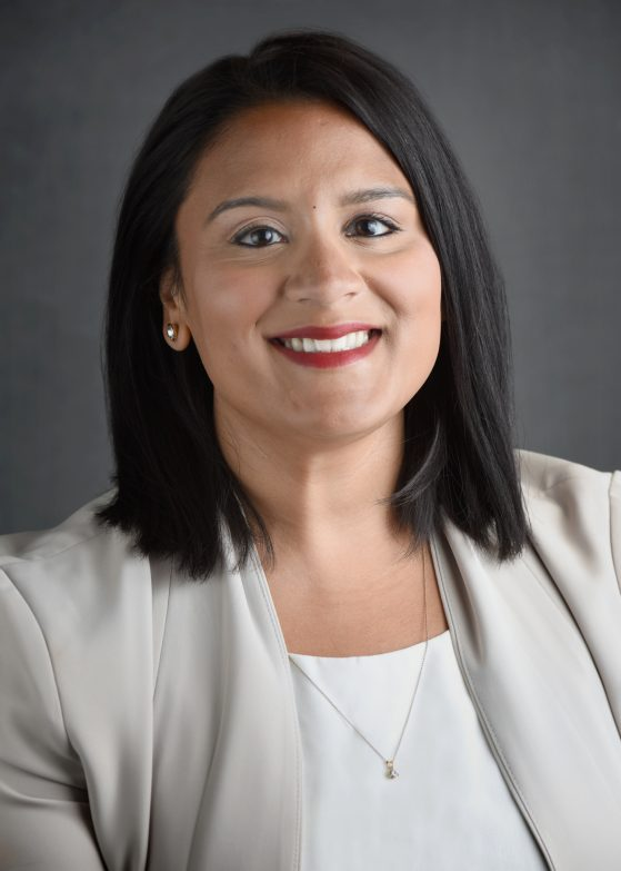 Nisha Pasupuleti has brown eyes, black straight hair to her shoulders, wearing a white shirt and tan blazer. sitting in front of a gray background.