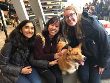 three students posing with corgi