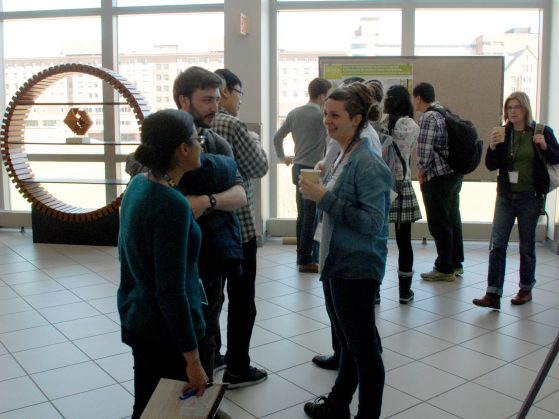 Graduate students mingle during the poster session.