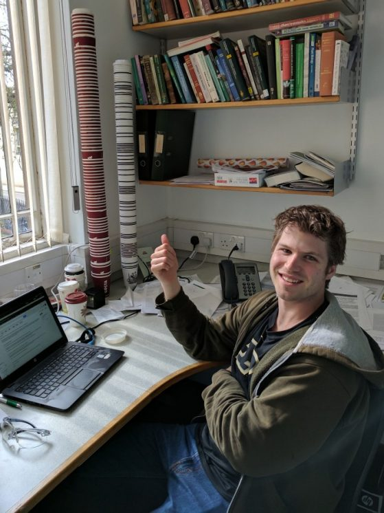 Joseph Walker in a lab with coffee cup towers.