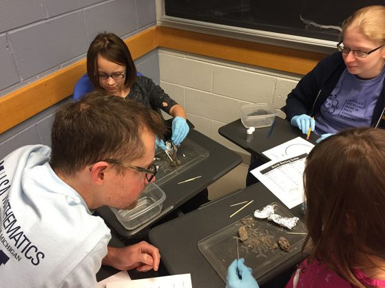 EEB graduate student Gordon Fitch helps students dissect owl pellets.
