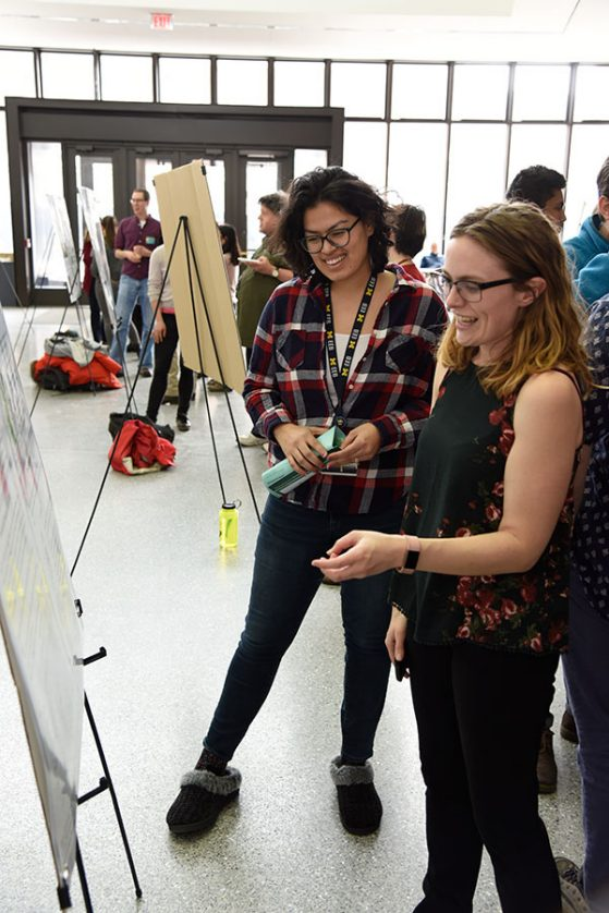 EEB graduate student Susanna Campbell (left) explores the poster session.