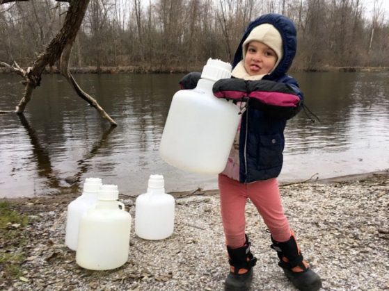 Duhaime's daughter, Aurora, helping to collect water samples from the Huron River.