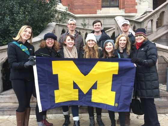 group of U-M students on the steps of a building in Helsingborg, Sweden, holding a U-M maize and blue flag