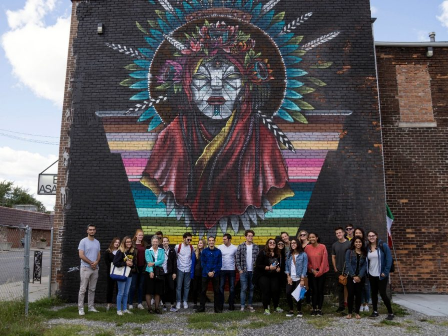 In Detroit's Mexicantown, History 328 pose in front of a Victor Quiñonez (aka Marka27) mural. (Photo: Marian Krzyzowski)