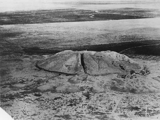 Black and white aerial view of a large earthen mound in a desert context.