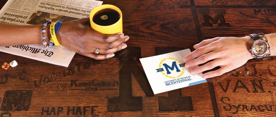 Two hands on a table that has block M, names, and other graffiti carved into its surface. One hand it touching a 20 questions with LSA playing card. The other hand is holding a cup of coffee in a yellow mug.