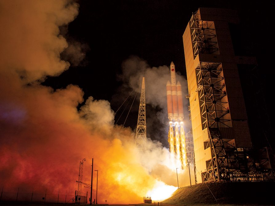 A photograph of the launch of the Parker Solar Probe. A chain of fire extends from the rocket to the earth and red and yellow billowing plumes of smoke drift up around it.