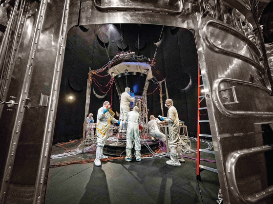 Six people in white covered suits that include their heads and feet stand together working on a large structure covered with wires. All things considered, the solar probe is pretty small—about 1,300 pounds and the size of a small car