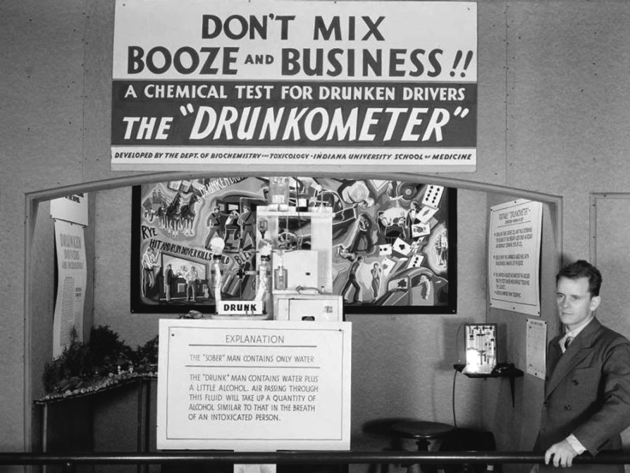 "A man stands off to the side of what looks like a booth advertising the new ""drunkometer"" invention. He's surrounded by lots of informational signs. The largest of them all, above the booth, says, ""Don't mix booze and business!! A chemical test for drunken drivers: the 'Drunkometer'. Developed by the dept. of biochemistry and toxicology, Indiana University School of Medicine."""