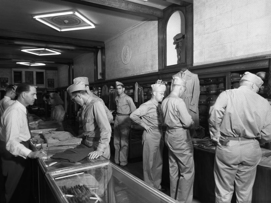 A black-and-white photo of men in military uniform who are browsing through the clothing store Van Boven.