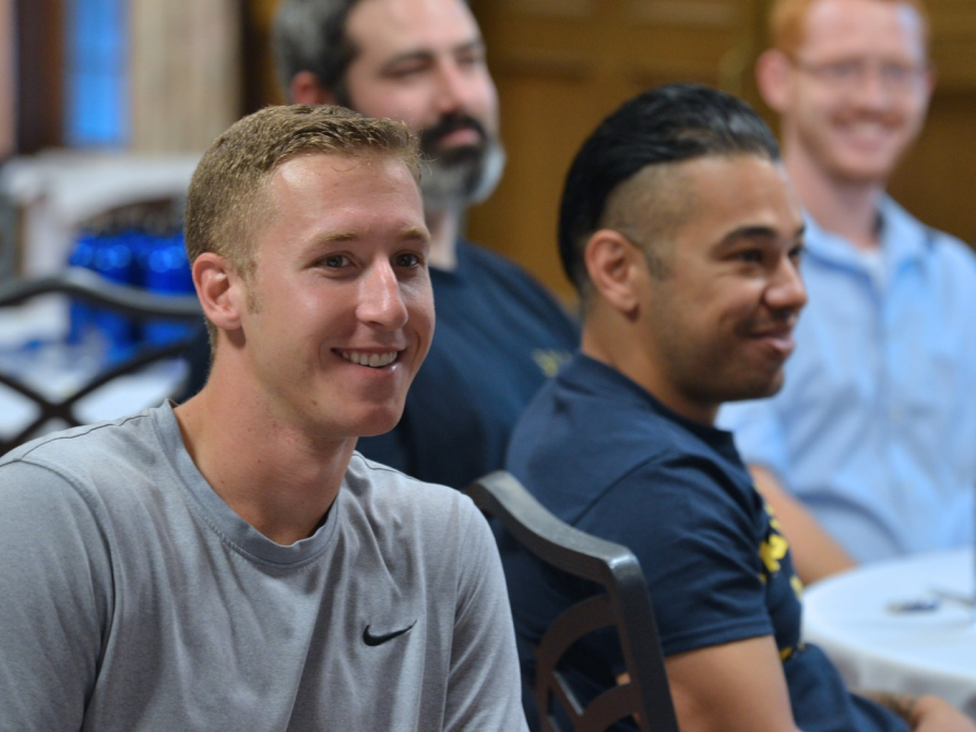 A classroom photograph in which two men are primarily featured. They are both smiling and attentive. Other men are included in the photo in the background.