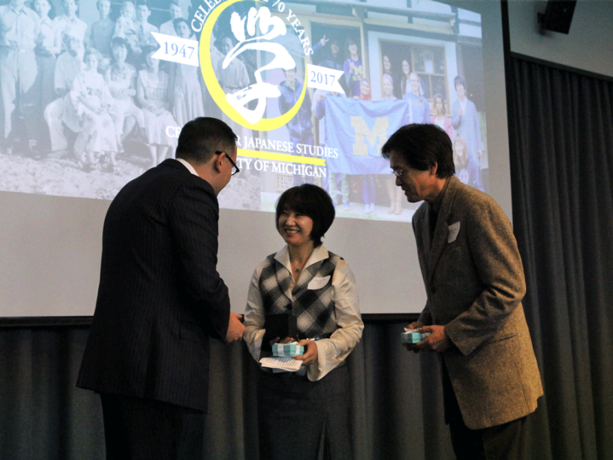 Mayumi and Masao Oka are facing LSA Dean Andrew Martin onstage. They are each holding light blue boxes tied with ribbon. The Center for Japanese Studies logo is on the screen behind them.