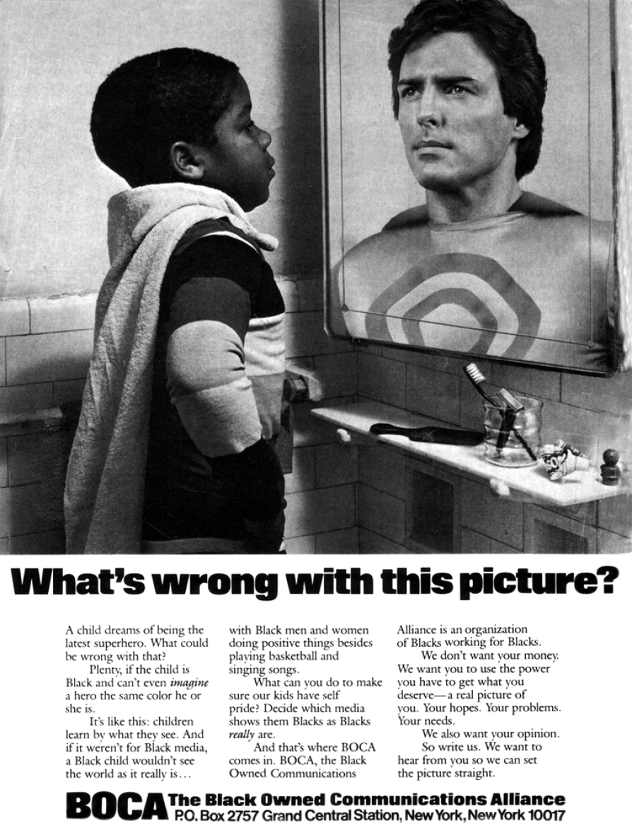 A black-and-white newspaper advertisement that depicts a young black boy wearing cape who is looking into a mirror where a white Christopher Reeve as Superman is there, looking back. Text below the image says, What is wrong with this picture?