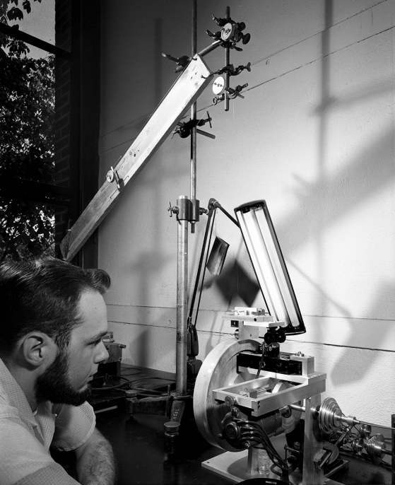 A black-and-white photograph of a man leaning intently toward a mechanical-looking device with his left elbow on the table.