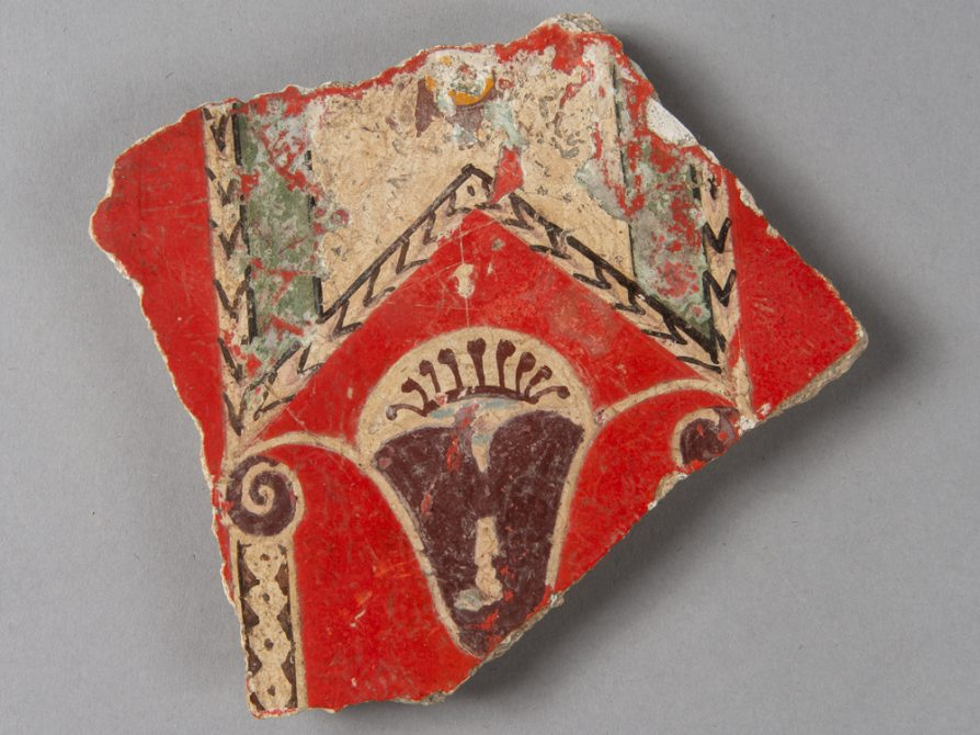 A trapezoid-shaped shard of pottery with a bright red background, filigreed geometric lines and a brown vase.