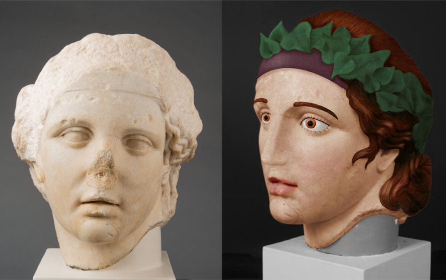 Two busts; one is the typical pale white color and has a broken nose. Next to it is a bust that is colored -- skin, the eyes, the lips, etc. There is a laurel wreath in the hair.