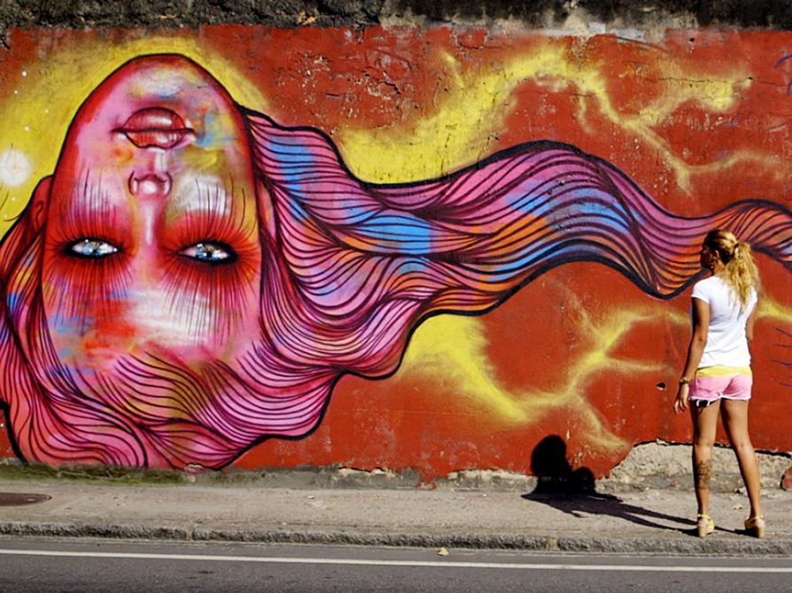 a wall mural of a woman's head and hair that is upside down. Her hair is flowing pink and orange and blue, and her face is shaded pink, gold, red, white, and yellow. A woman is standing on the sidewalk looking at it.