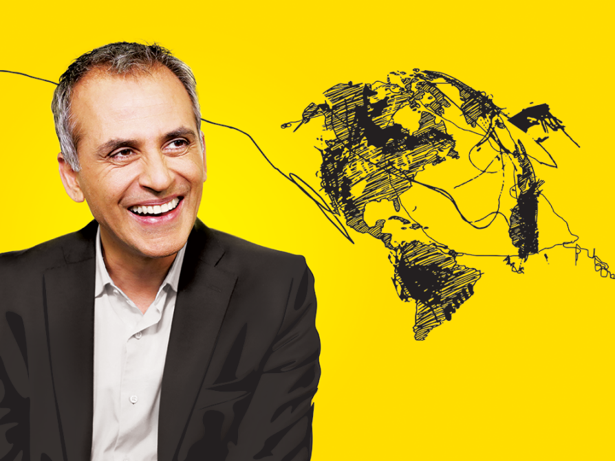 a photograph of Sanjay Varms wearing a dark coat and a light shirt looking to his left and laughing. The photo is against a yellow background, which has a rough drawing of the globe with disorganized squiggles and lines between the continents and going totally off the page in both directions.