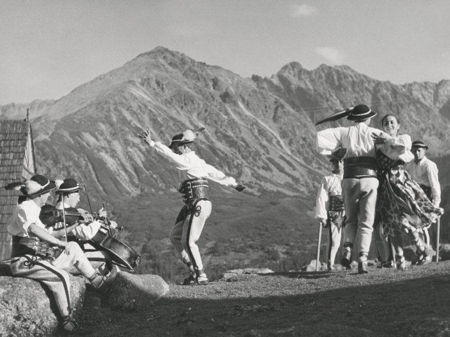 A black and white photo of people dancing on a ridge with a range of the mountains behind them at a distance. The people are wearing costumes: the men wear feathered caps and hold poles; the woman wears a dress with a long full skirt. At the left edge of the photograph, one man is playing a cello and the other is playing a violin.