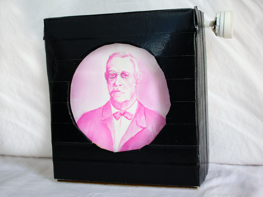 A photograph of a layered black square with a round cutout that features a pink image of a man in 19th century dress -- a Victorian cravat and jacket -- wearing small spectacles