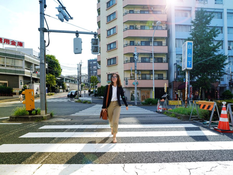 Hannah Dang walking through a crosswalk in a large city carrying a briefcase.