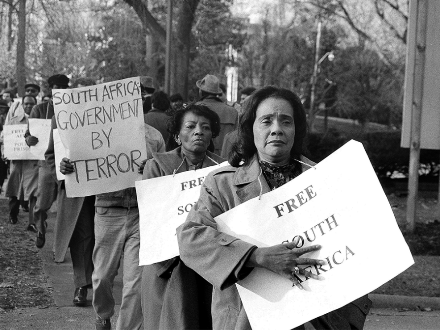 Black and white photograph of a line of marching protesters carrying signs that say free South Africa and South Africa government by terror. The marchers are wearing warm coats and the signs are hung by strings around their necks as if they were necklaces. Coretta Scott King is at the front of the line. She's looking into the distance and is holding the sign against her body with her open right hand.