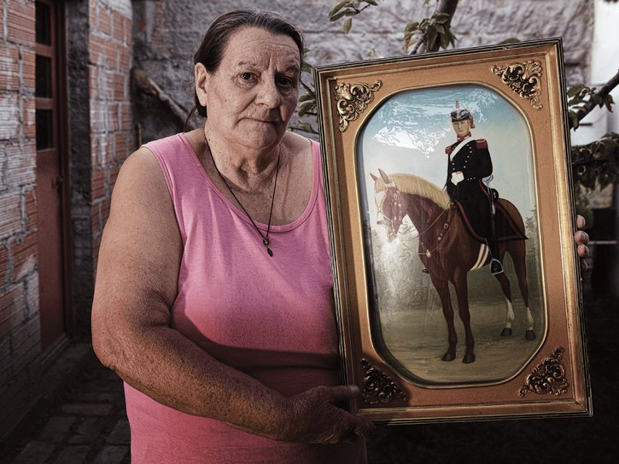 Photograph of Catalina Dickason holding a portrait of her ancestor on horseback.