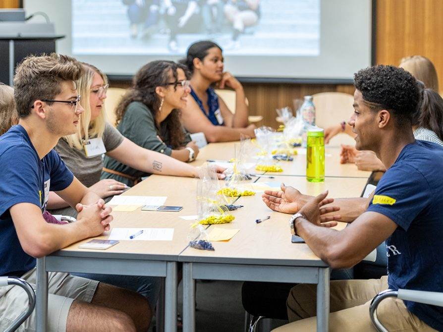 Students sitting together at either end of a long table. There are bags of blue and yellow M&M candies in plastic bags between them.