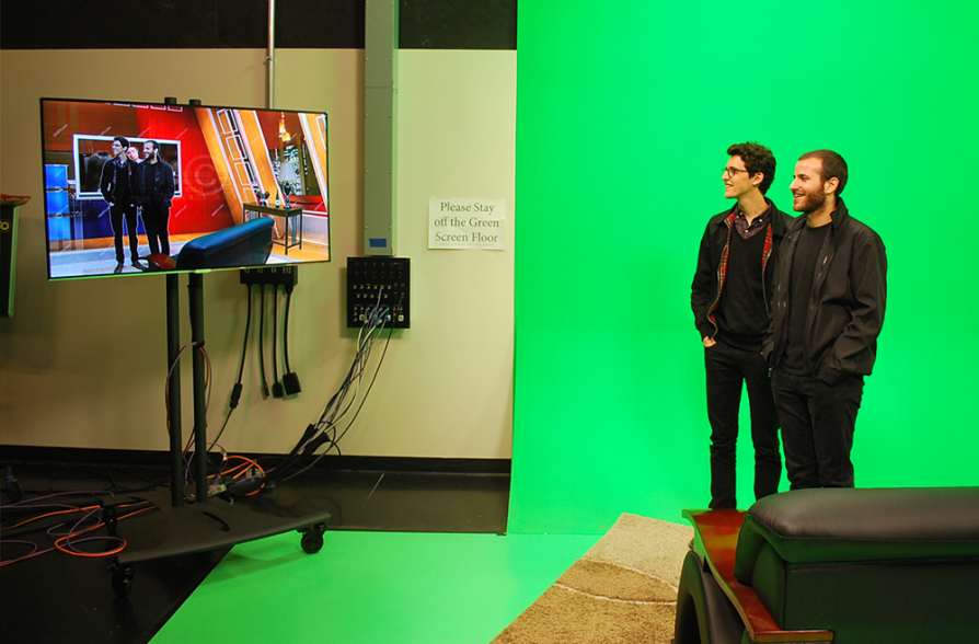 Two young men stand on a green floor in front of a green wall. They are looking at a television screen that mirrors them, but shows them in a room similar to a television news studio.