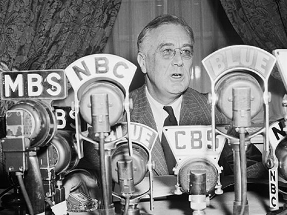 Black and white photograph of Franklin D Roosevelt speaking behind NBC, CBS and many other microphones.