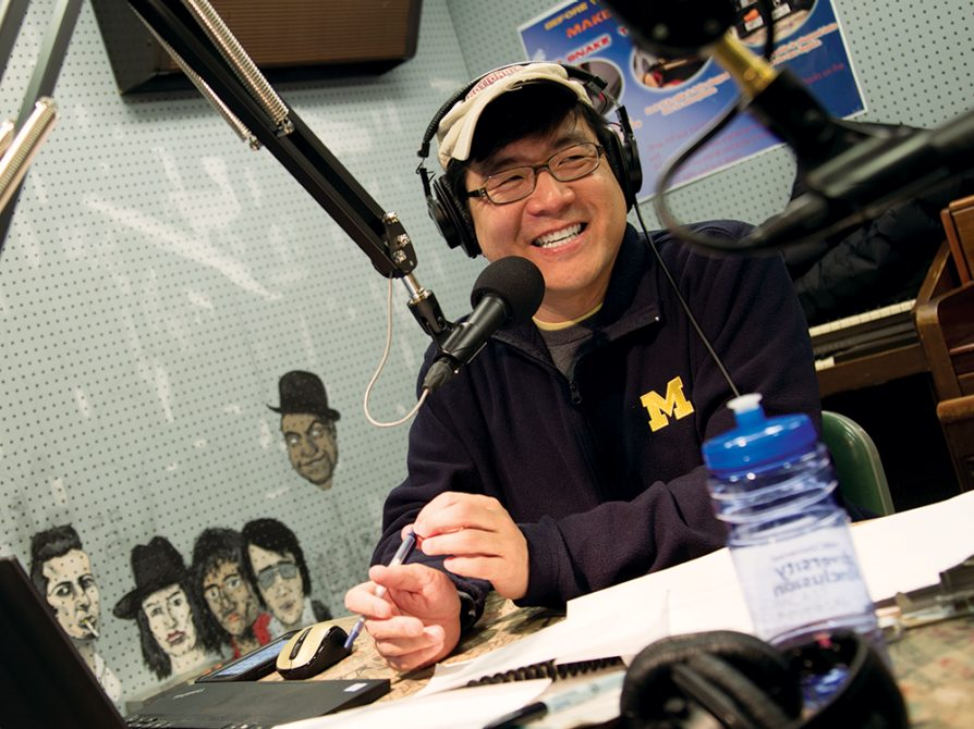 Robert Yoon behind the mic at WCBN. He's wearing headphones, a baseball hat, and a U-M fleece, and he's smiling at someone off camera.