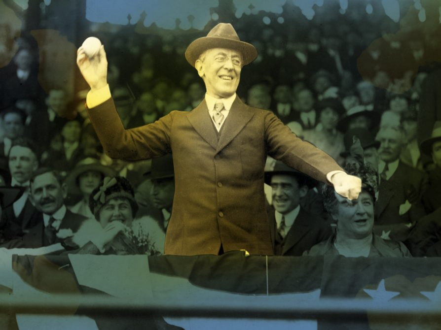 A picture of Woodrow Wilson preparing to throw a baseball in front of a crowd. The crowd is tinted blue and Wilson is vibrantly colored -- brown suit and hat, his right arm cocked for a pitch. He has a smile on his face.
