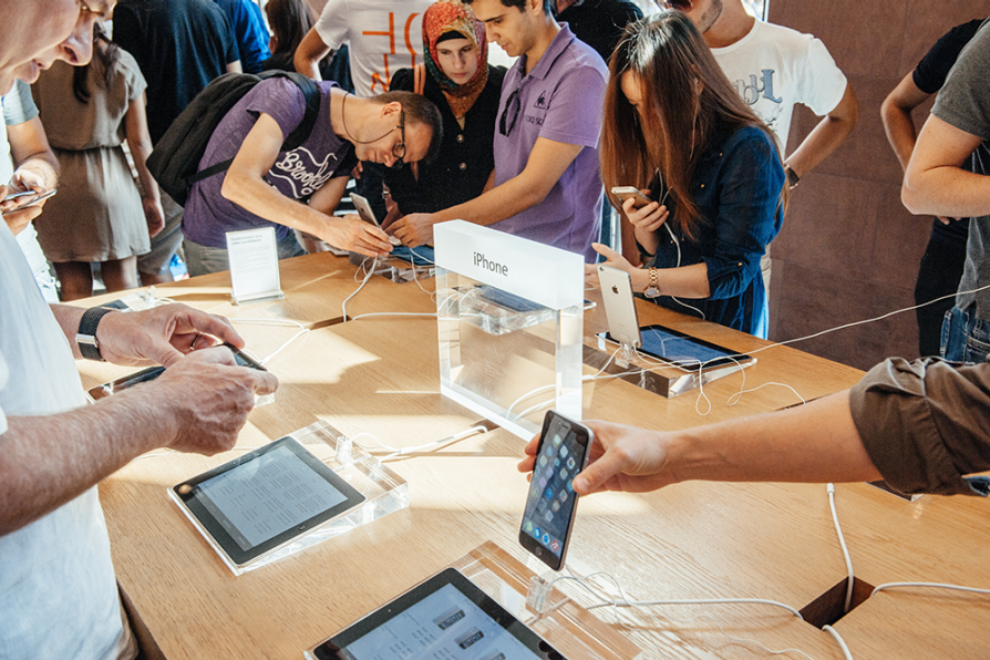 Shoppers at an Apple store investigating iPads and iPhones